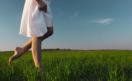 緑の草の牧草地の上を歩いて白いドレスの若い女性
