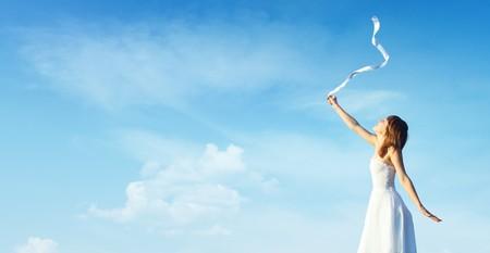 Mujer joven en vestido blanco con lazo blanco sobre fondo azul cielo nublado