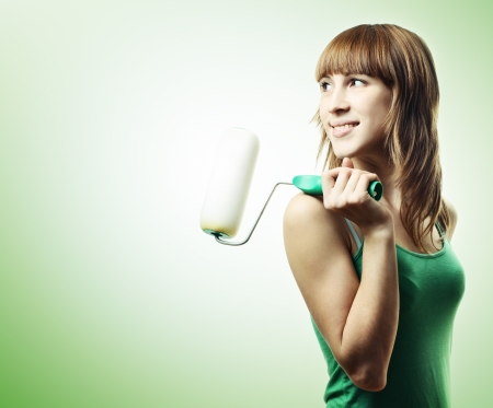 renovation de maison: Jeune femme avec un pinceau de rouleau sur fond vert  Banque d'images