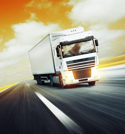 Camion blanche sur route asphaltée sous le ciel de résumé rouge avec des nuages  Banque d'images