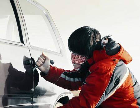 Puerta de ruptura de hombre joven de un coche