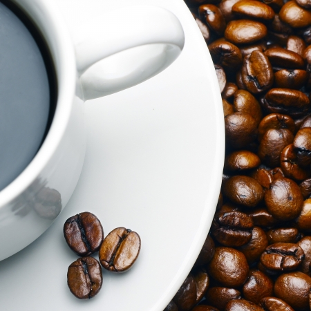 Cup with coffee on plate and beans Stock Photo