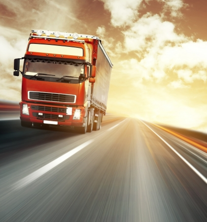 lorry: Red truck on blurry asphalt road under red sky with clouds and sunset light