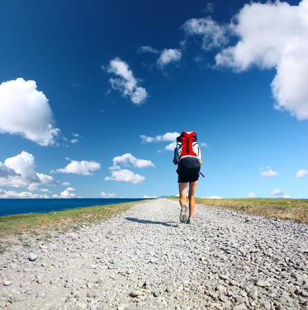 Travel Backpack: Caminando sobre la carretera bajo un cielo azul con nubes de mochileros