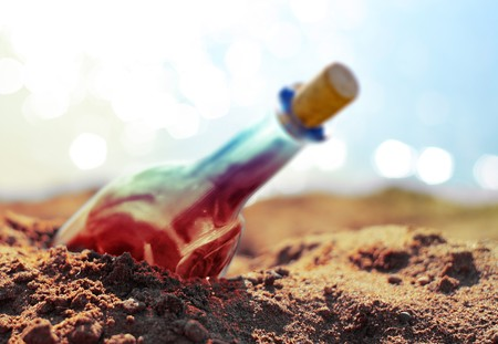 Colored bottle in sand on beach photo