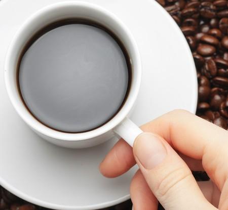 カップのコーヒー、コーヒー豆の背景を持つ手