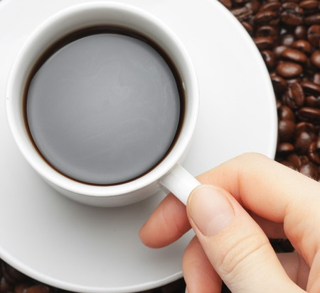 people drinking coffee: Cup with coffee and hand with coffee beans background Stock Photo