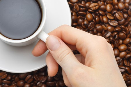 fingers on top: Cup with coffee and hand over coffee beans background