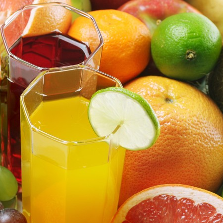 Ripe tropical fruits and glasses with juice photo