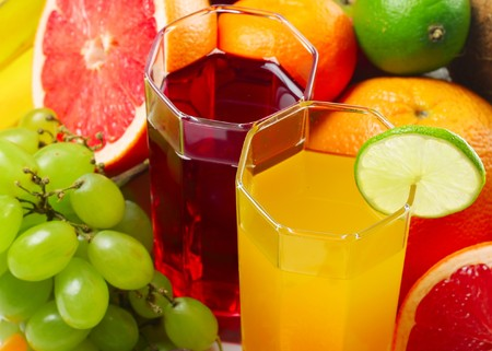 Fruits and slices near glasses with juice photo