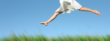 Woman in white dress jumping over green blurred grass Stock Photo - 7293954