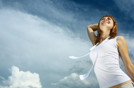 Young smiling woman in white enjoing the sun over blue sky background photo