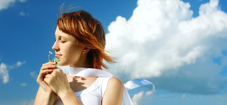 Young woman with flower and blue sky with clouds photo