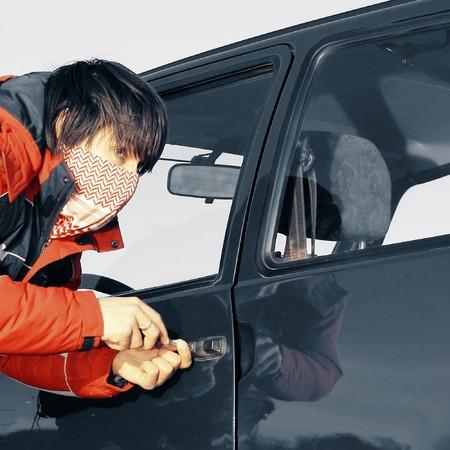Young man breaking door of a car photo