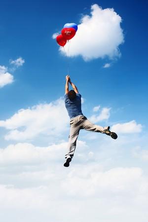 Hombre joven volando en azul cielo nublado con globos de colores