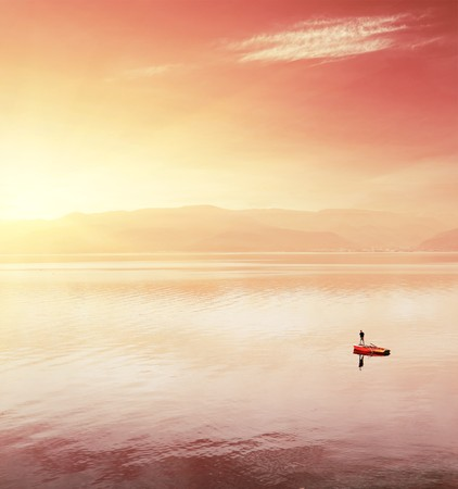 Alone fisherman in boat on huge lake under sunst light photo