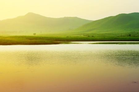 lagos: R�o y monta�as con hierba verde bajo luz sunset  Foto de archivo