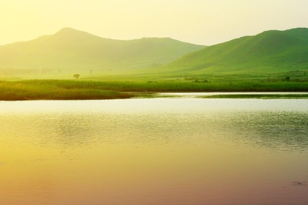 sea side: River and mountains with green grass under sunset light Stock Photo