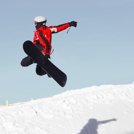 Snowboard sportsmen in jump over clear blue sky photo