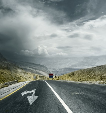 asphalt road: Asphalt road in mountains with arrows and storm dark clouds over valley