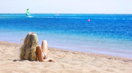 beach blond hair: Young blonde woman lying on sand near sea Stock Photo