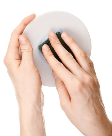 Hands with sponge and plate over white photo