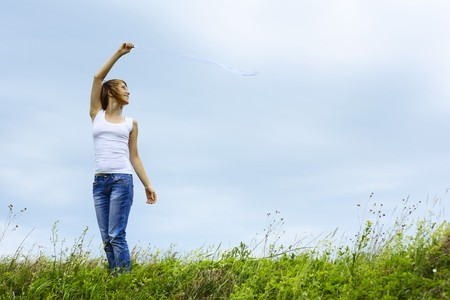 Alone woman with thin robbon standing on meadow with grass over sky background