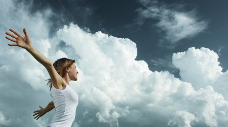 Young woman with raised hands over cloudy background photo