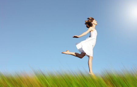 Young woman in white dress jumping over green grass photo