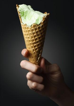 Icecream cone in hand over black background photo
