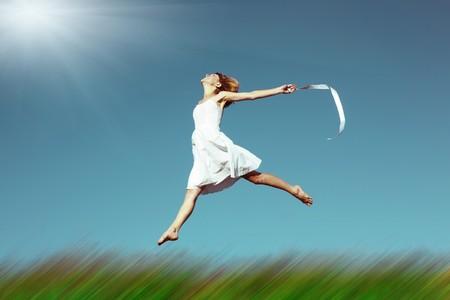 若い女性とぼやけの草草原を飛び越して