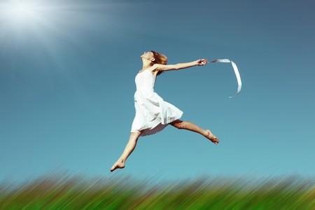enjoy space: Young woman jumping over meadow with blurred grass