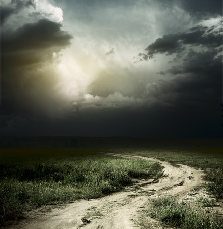 dirt road: Rural road and dark storm clouds Stock Photo