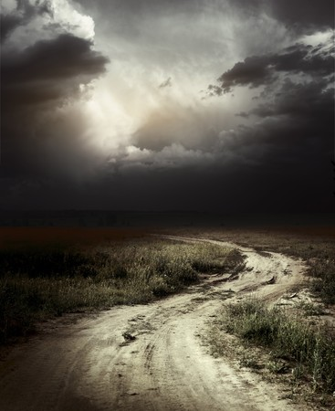 view through: Rural road and dark storm clouds Stock Photo