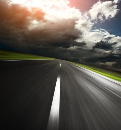 light speed: Carretera asfaltada vac�a y cielo nublado con luz solar