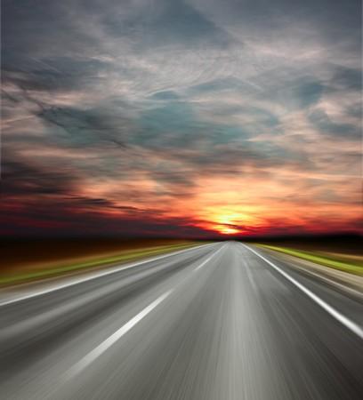 Sunset over blurred asphalt road photo