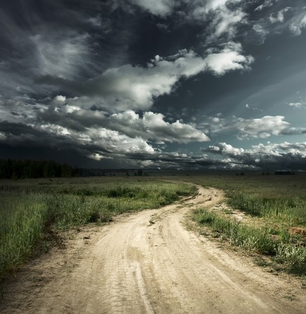 rural road: Road in field and stormy clouds Stock Photo