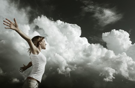 over: Young woman with raised hands over stormy clouds background