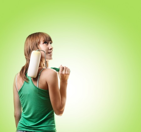 Young woman with roller brush over green background photo