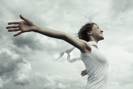 Young woman with raised hands over clouds background photo