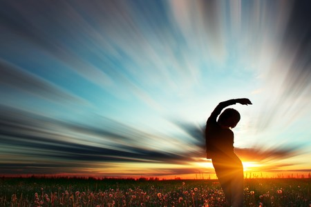 inclination: Young woman standing on meadow with herbs under sunset lights Stock Photo