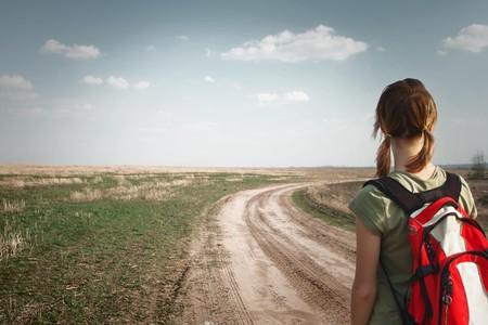どこかに探している農村部の道路上のバックパックを持つ若い女 写真素材