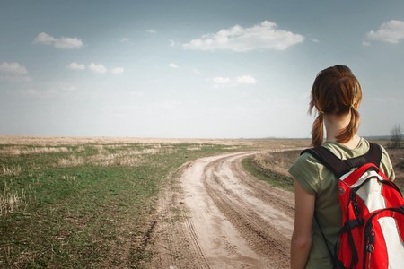 somewhere: Young woman with backpack on rural road looking to somewhere Stock Photo