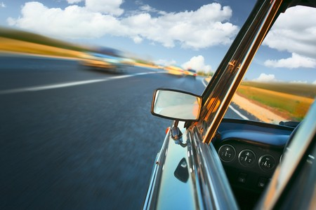 tilt views: Car with mirror and dashboard on blurred asphalt road with another cars Stock Photo