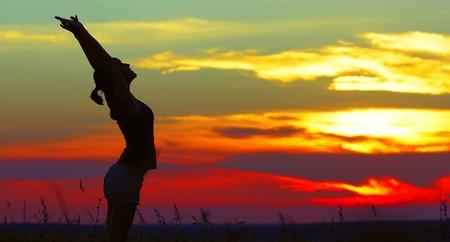 夕日の光の下で exersices を行う若い女性