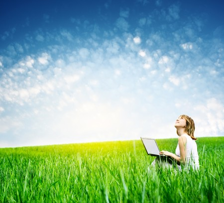woman sitting with laptop: Young woman with laptop sitting on green grass and looking to a sky