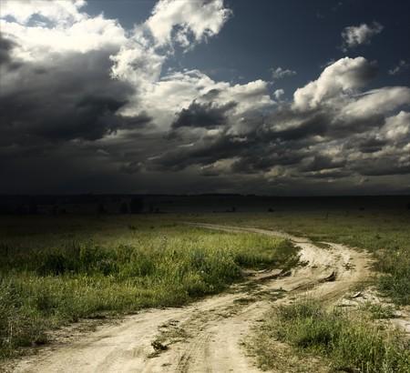 temp�te: Chemin dans le champ et les nuages orageuses