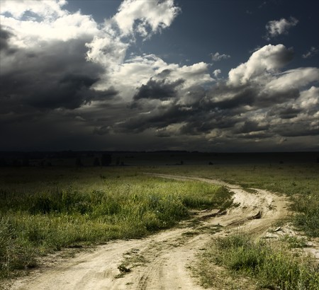 thunder storm: Road in field and stormy clouds Stock Photo