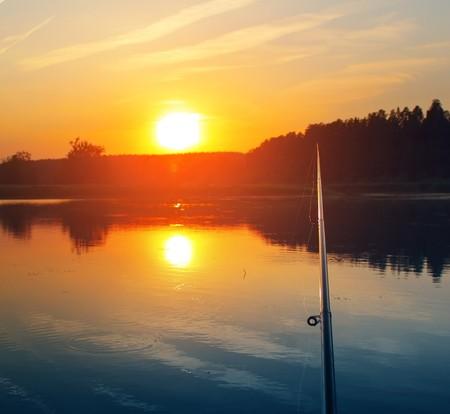 bobber: Fishing rod sunset and bobber on water