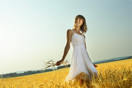 Young woman in white dress standing in field with wheat photo